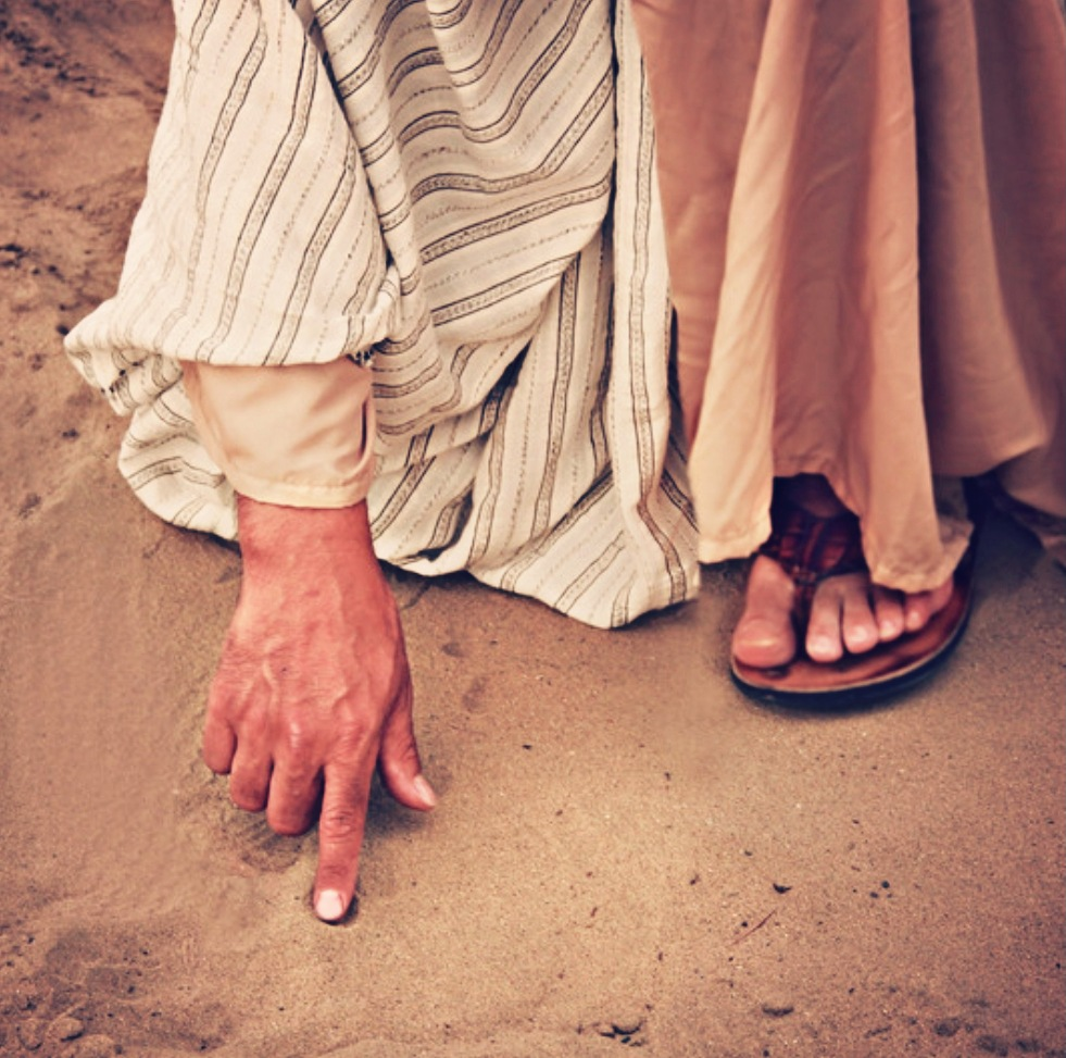 Jesus bends down and draws in the sand.