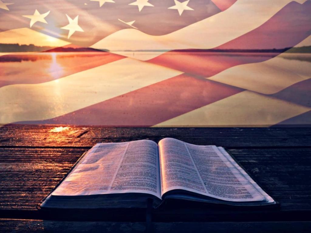 A Bible lies open under an American flag.